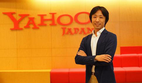 ヤフー株式会社 eコマース革命 エバンジェリスト 白山 達也さんがYahoo!Japanのロゴの前で腕を組んで写っているプロフィール写真